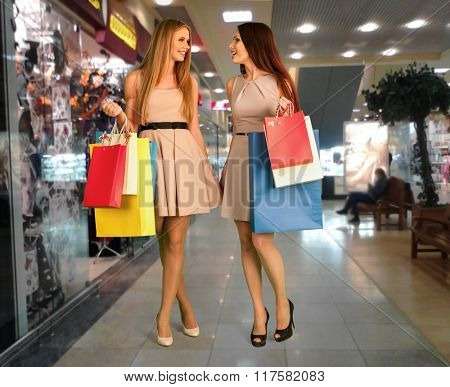 Women holding shopping bags are  doing purchase at  shop center.