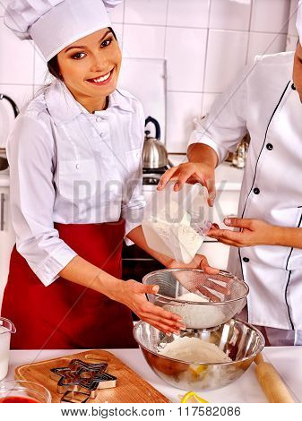 Portrait of happy woman and chef man in hat cooking dough on professional kitchen.