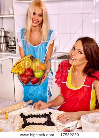 Young women  baking cookies with fruits in oven.