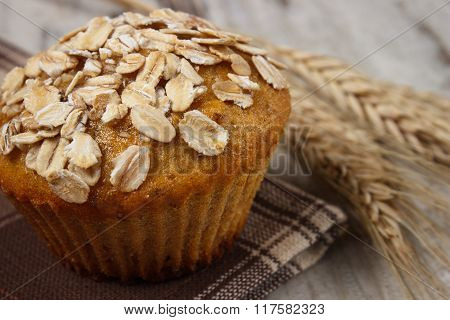 Fresh Muffin With Oatmeal And Ears Of Rye Grain On Checkered Tablecloth, Delicious Healthy Dessert