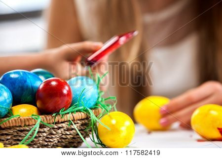 Children paint Easter eggs at home. Sharpness on rainbow eggs. Blurry girl background.