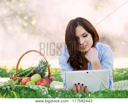 Young attractive lady lying on a mat in the park browsing her tablet.