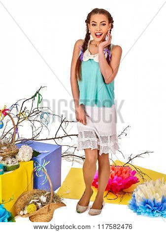 Woman full-length in easter spring style holding eggs and  in basket.