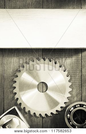 circular saw blade on wooden background texture