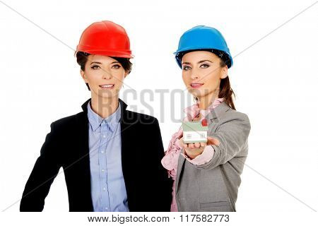 Two architects women with house model.