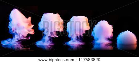 Different color smoke explosions isolated on black background