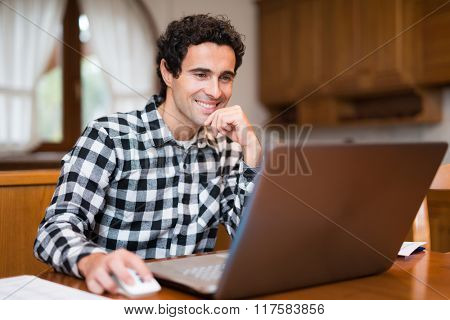 Happy man using his laptop at home