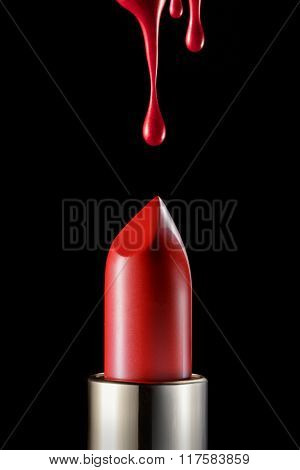 Red melting lipstick isolated on black background with drips on top