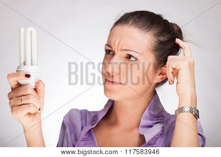 Puzzled woman looking at an eco-save bulb