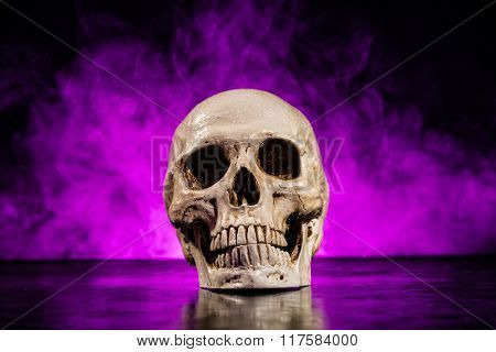 Old human skull head with smoke on dark background