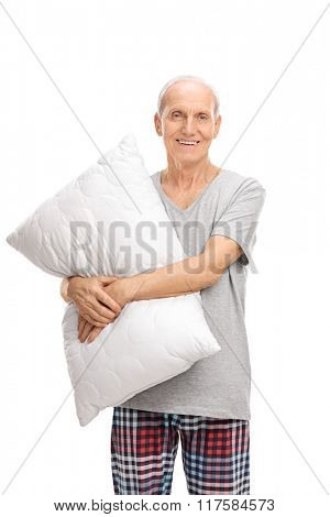 Vertical shot of a senior man hugging a pillow and looking at the camera isolated on white background