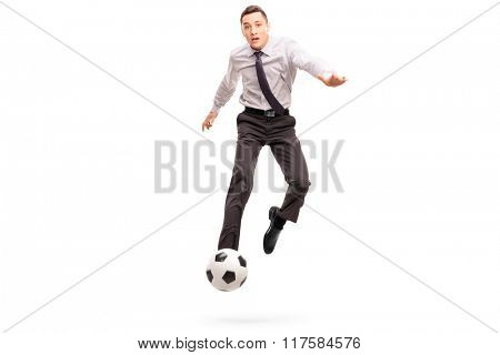 Studio shot of a young businessman kicking a football shot in midâ??air isolated on white background