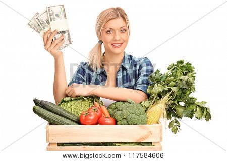 Young female agricultural worker holding a few stacks of money and standing behind a crate with vegetables isolated on white background