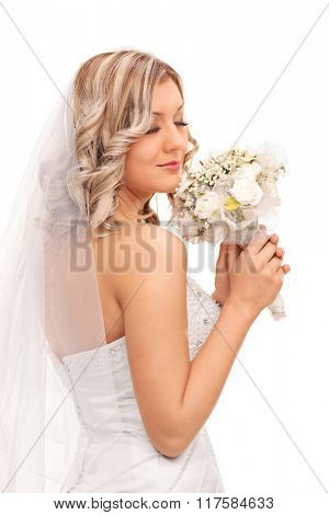Vertical shot of a beautiful blond bride smelling wedding bouquet isolated on white background
