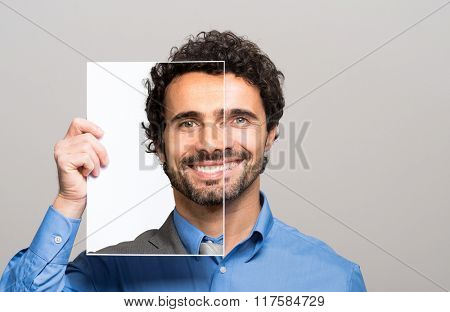 Happy man covering half his face with an image of himself
