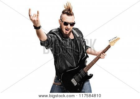 Studio shot of a punk rock guitarist playing guitar and making rock gesture isolated on white background