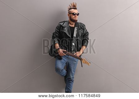 Young punk rock guitarist in black leather jacket holding a guitar and smoking a cigarette