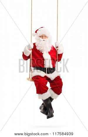 Full length portrait of Santa Claus swinging on a wooden swing and smiling isolated on white background