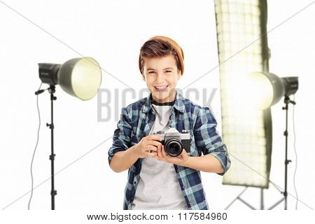 Joyful little boy holding a camera and standing in a studio with lighting equipment isolated on white background