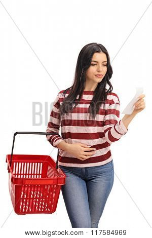 Vertical shot of a young woman holding a shopping basket and reading the shopping list isolated on white background