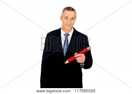 Manager writing with an oversized red pencil