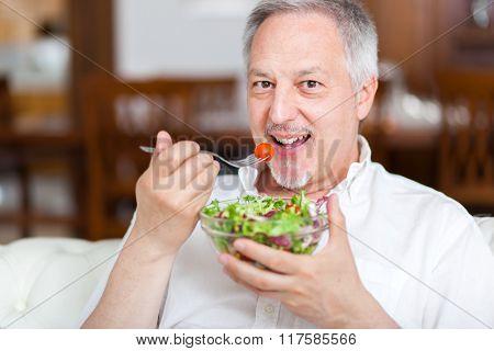Mature man eating a healthy salad