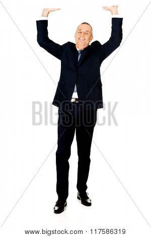 Full length businessman pushing invisible ceiling