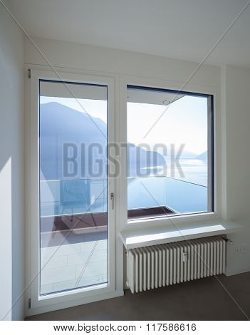 Empty room in modern house, window with lake landscape