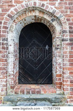 A black wooden door on a brick wall