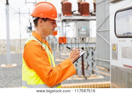 young electrician taking machine readings in substation