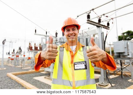 handsome electrician with thumbs up at substation