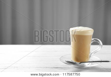 Milk coffee in glass cup with spoon on light wooden table