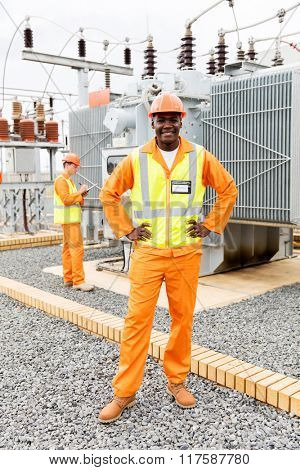 african american electrical technician with colleague on background in substation