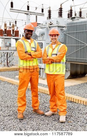 happy industrial engineers with arms crossed in substation