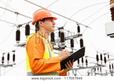 male electric engineer standing in electricity power plant