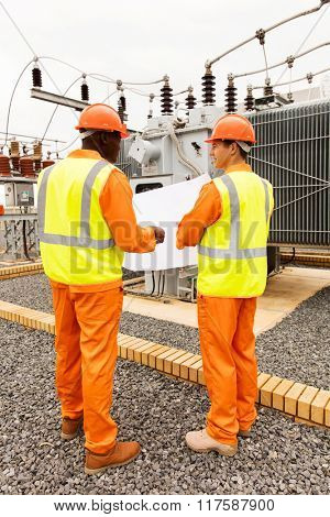rear view of industrial engineers discussing blueprint at substation