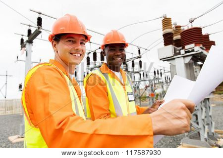 two professional multiracial electricians holding blueprint in substation