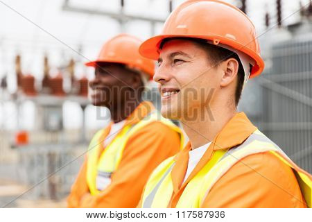 handsome electrical engineer looking away with colleague on background