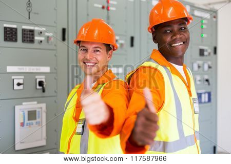 two handsome power company technical co-workers with thumbs up