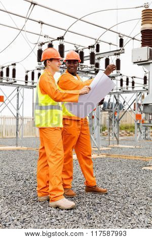 electrical engineer holding blueprint in electric substation