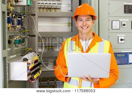 portrait of professional industrial technician in front of machinery control panel