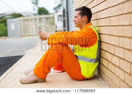 relaxed electrician using smart phone during break