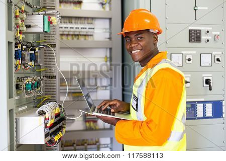 african electrical worker using laptop computer checking transformer