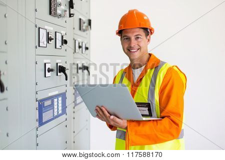portrait of young engineer with laptop in control room