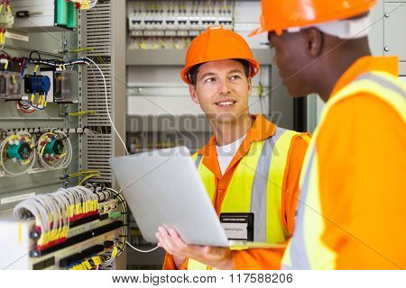 electrical engineers adjusting transformer settings in control room