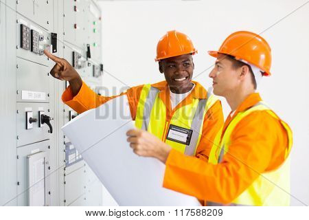two industrial technicians working in control room