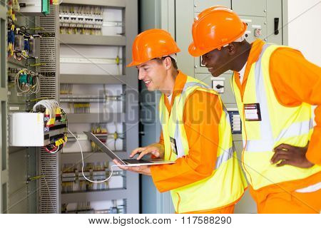 professional industrial technicians checking control box status with laptop computer