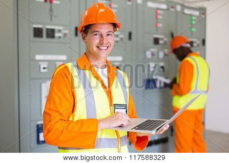 happy electrical technician using laptop in power plant control room