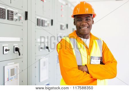 cheerful african industrial technician in substation control room