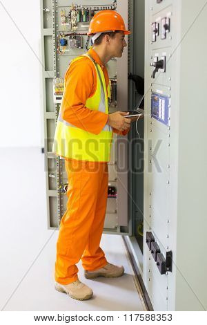 industrial programmer checking computerized machine status with laptop computer